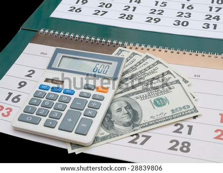 Calendar, calculator and several one hundred American dollar bills