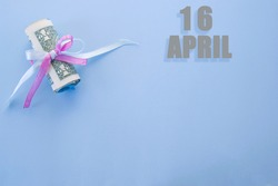 calendar date on blue background with rolled up dollar bills pinned by blue and pink ribbon with copy space. April 16 is the sixteenth day of the month.