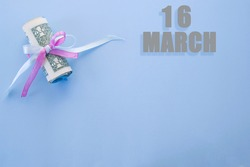 calendar date on blue background with rolled up dollar bills pinned by blue and pink ribbon with copy space. March 16 is the sixteenth day of the month.
