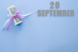 calendar date on blue background with rolled up dollar bills pinned by blue and pink ribbon with copy space. September 20 is the twentieth day of the month.