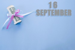 calendar date on blue background with rolled up dollar bills pinned by blue and pink ribbon with copy space. September 16 is the sixteenth day of the month.