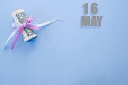 calendar date on blue background with rolled up dollar bills pinned by blue and pink ribbon with copy space. May 16 is the sixteenth day of the month.