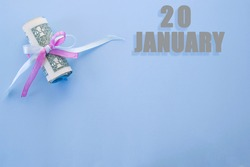 calendar date on blue background with rolled up dollar bills pinned by blue and pink ribbon with copy space. January 20 is the twentieth day of the month.