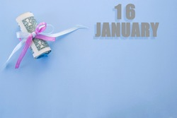 calendar date on blue background with rolled up dollar bills pinned by blue and pink ribbon with copy space. January 16 is the sixteenth day of the month.