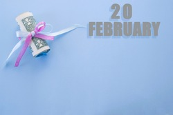 calendar date on blue background with rolled up dollar bills pinned by blue and pink ribbon with copy space. February 20 is the twentieth day of the month.