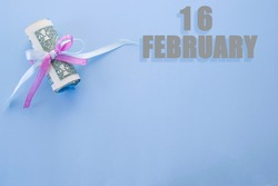 calendar date on blue background with rolled up dollar bills pinned by blue and pink ribbon with copy space. February 16 is the sixteenth day of the month.