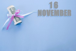 calendar date on blue background with rolled up dollar bills pinned by blue and pink ribbon with copy space. November 16 is the sixteenth day of the month.