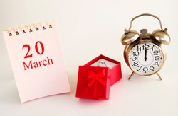 calendar date on light background with red gift box with ring and alarm clock with copy space. March 20 is the twentieth day of the month.