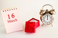 calendar date on light background with red gift box with ring and alarm clock with copy space. March 16 is the sixteenth day of the month.