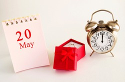 calendar date on light background with red gift box with ring and alarm clock with copy space. May 20 is the twentieth day of the month.