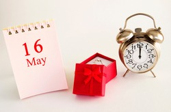 calendar date on light background with red gift box with ring and alarm clock with copy space. May 16 is the sixteenth day of the month.