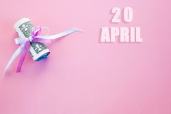 calendar date on pink background with rolled up dollar bills pinned by pink and blue ribbon with copy space. April 20 is the twentieth day of the month.