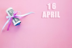 calendar date on pink background with rolled up dollar bills pinned by pink and blue ribbon with copy space. April 16 is the sixteenth day of the month.
