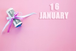 calendar date on pink background with rolled up dollar bills pinned by pink and blue ribbon with copy space. January 16 is the sixteenth day of the month.
