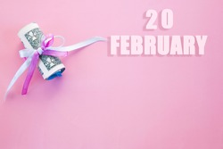 calendar date on pink background with rolled up dollar bills pinned by pink and blue ribbon with copy space. February 20 is the twentieth day of the month.