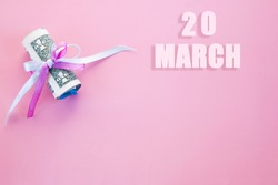 calendar date on pink background with rolled up dollar bills pinned by pink and blue ribbon with copy space. March 20 is the twentieth day of the month.