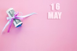 calendar date on pink background with rolled up dollar bills pinned by pink and blue ribbon with copy space. May 16 is the sixteenth day of the month.