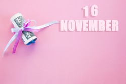 calendar date on pink background with rolled up dollar bills pinned by pink and blue ribbon with copy space. November 16 is the sixteenth day of the month.
