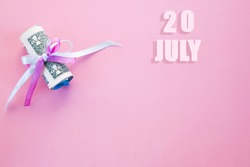 calendar date on pink background with rolled up dollar bills pinned by pink and blue ribbon with copy space. July 20 is the twentieth day of the month.