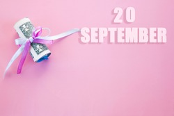 calendar date on pink background with rolled up dollar bills pinned by pink and blue ribbon with copy space. September 20 is the twentieth day of the month.