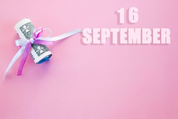 calendar date on pink background with rolled up dollar bills pinned by pink and blue ribbon with copy space. September 16 is the sixteenth day of the month.