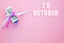 calendar date on pink background with rolled up dollar bills pinned by pink and blue ribbon with copy space. October 20 is the twentieth day of the month