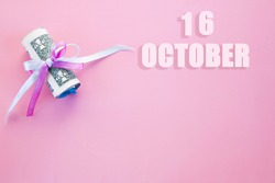 calendar date on pink background with rolled up dollar bills pinned by pink and blue ribbon with copy space. October 16 is the sixteenth day of the month