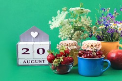 Calendar for August 20 : the name of the month of August in English, cubes with the number 20, bouquets of wild flowers, jars of jam, strawberries and cherries in cups, green background