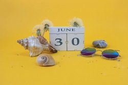 Calendar for June 30: cubes with the number 30, the name of the month of June in English, shells, sea stones, sunglasses, faded dandelions on a yellow background