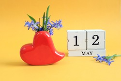 Calendar for May 12 : a bouquet in a heart-shaped vase with blue flowers and the numbers 12 on cubes, the name of the month of May in English, yellow background