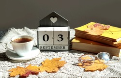 Calendar for September 3 : the name of the month in English, cubes with the numbers 0 and 3, a cup of tea, books, maple leaves on a gray openwork napkin, side view, gray background