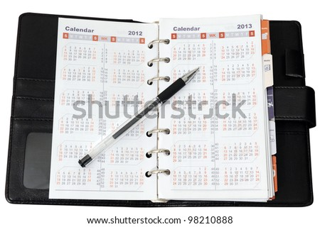 Calendar in notebook with a pen on it