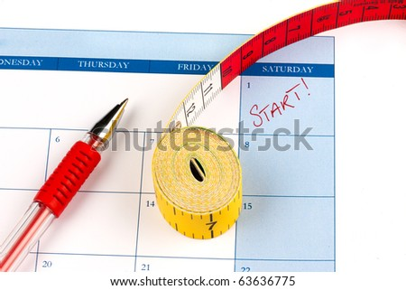 Calendar marking the 1st of the month with a rolled tape measure and pen