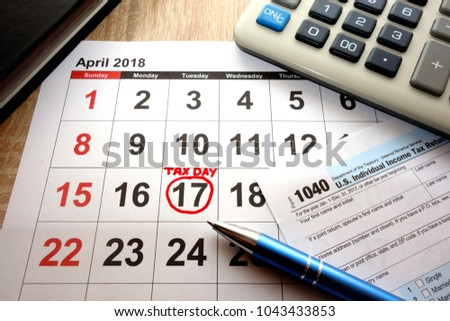 Calendar on office desk showing date April 17 2018 and 1040 form, tax day in USA concept