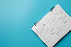 Calendar on solid blue background with copy space, business meeting schedule, travel planning or project milestone and reminder concept.