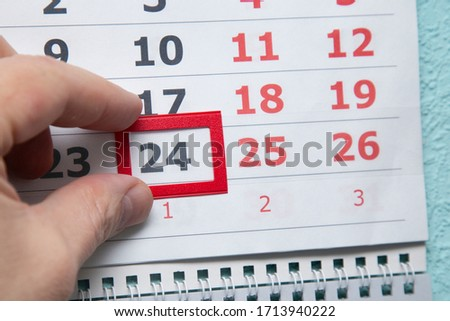 Calendar on the wall. An everyday paper calendar that is moved by a human hand. Photo stock ©