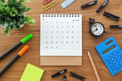 Calendar on wooden table with clock and calculator from top view