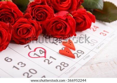 Calendar page with the red hearts  and  bouquet of red roses on February 14 of Saint Valentines day. #366952244