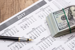 calendar with a pen and dollars.