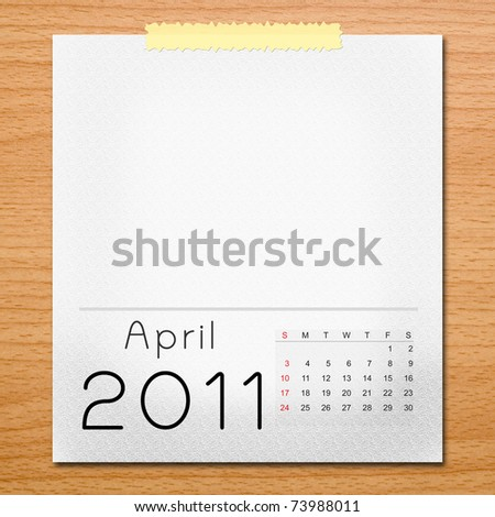 Calendar 2011 with tape on wooden background. April