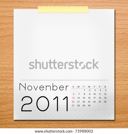 Calendar 2011 with tape on wooden background. November