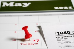 Calendar with Tax Day note inserted in the date for May 17 to illustrate the new tax return filing date of 17th May 2021.