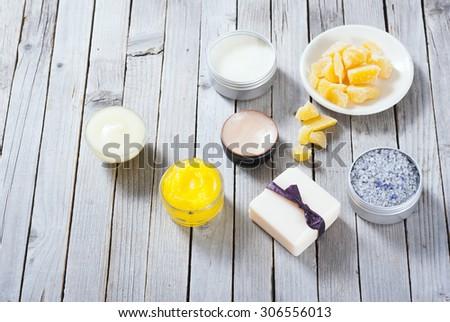 Calendula cream, lip balm, raw bees wax, bath salt soap and other cosmetics on rusty wood table