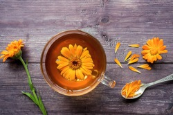 Calendula (Marigold) herbal tea with fresh plant and flowers on wooden table. Top view