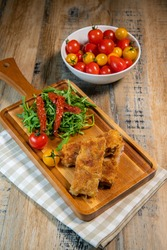 Calf escutcheon recipe for Milanese, Parmesan, Roquette and candied tomatoes