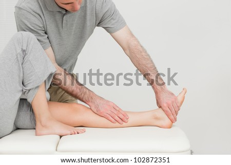 Calf of a patient being stretched by a doctor in a room