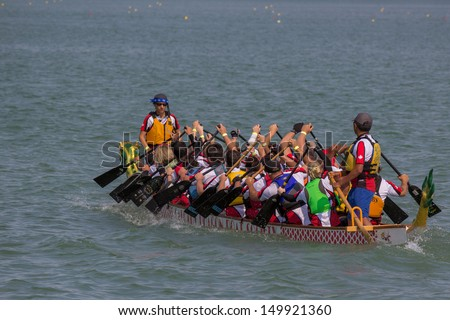 CALGARY, CANADA - AUGUST 11: A Dragon Boat team works together in the annual Calgary Dragon Boat Race & Festival on 11 August 2013 at North Glenmore Park.