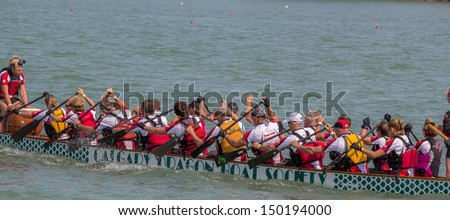 CALGARY, CANADA - AUGUST 11: Dragon Boat team works together in the annual Calgary Dragon Boat Race & Festival on 11 August 2013 at North Glenmore Park in Calgary.