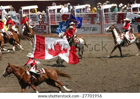 CALGARY, CANADA – CIRCA JULY 2004 Cowgirls gallop on horseback at Stampede Parade Calgary Alberta, circa July 2004 in Calgary. The first event was inaugurated in 1912 by American Guy Weadick.