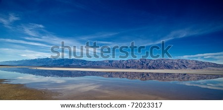 California mountains are reflected in collecting waters of Death Valley National Park.